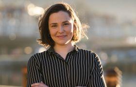 Marinbiolog Susanne Tonheim er avbildet utendørs. Bakgrunnen er dus, det er sol. Hun ser inn i kamera og smiler, og er iført svart- og hvitstripete bluse. Hun har mørkt, halvlangt hår.