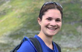Idrettskonsulent Nora Menous-Moland i blå T-skjorte og sort ryggsekk ute i naturen.