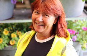 Portrettfoto av gartnar Gry F.T. Snildal. Avbilda frå brystet og opp, iført gul arbeidsjakke.