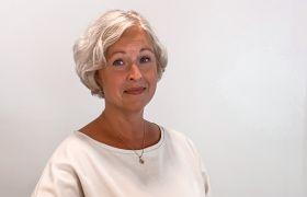 Markedsanalytiker Cecilie Natasha Henriksen i TINE sitter ved et bord med en bærbar PC foran seg.