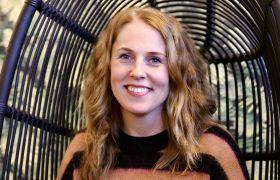Portrettfoto av journalist Sigrid Ringnes, ikledd stripete ullgenser, sittande i svart korgstol, avbilda frå brystet og opp.