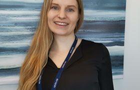 Portrett av Malin Sørli. Hun er avbildet fra livet og opp, i svart skjorte, med blågrått bilde i bakgrunnen.