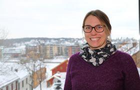 Portrett av revisor Kjersti Eik utendørs med hus og blokker i bakgrunnen.