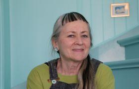 Portrett av Åse Schmidt, hun sitter i en trapp, iført selebukse og grønn genser.