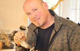 Portrett av taksidermist Bjørn Aksel Bjerke. Han holder en utstoppet fugl i ene hånden og en pinsett i den andre.