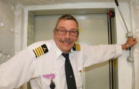 Hans Morten Rachløw i hvit uniformskjorte med fire striper på skulderklaffen, lener seg mot en dørkarm i motorrommet.