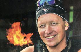 Smed Frank Abildsten smiler bredt med flammer i bakgrunnen.