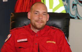 Ambulansearbeider Erik Ødegård sitter i en svart lenestol, han har på rød jobbuniform.