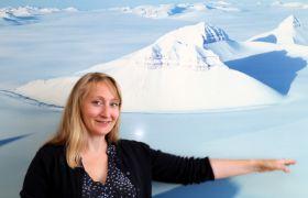Vigdis Lonar Barth er glad i Svalbard, og poserer foran et flott bilde av øya på kontoret på Norsk Romsenter.