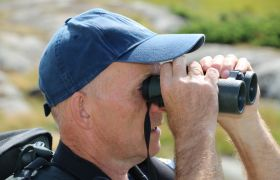 Per Espen Fjeld står med kikkert og ser på fugler i Vestfold. Han er vendt mot høyre og har en blå caps på hodet.