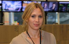 Eva-Therese Loob Grøttum i nyhetsredaksjonen til VG i Oslo. Hun har en beige bluse på seg og ser i kameraet. I bakgrunnen henger det skjermer med ulike nyhetsrelaterte sendinger.
