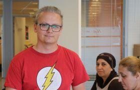 Anders Gran ser i kameraet. Han har på en rød T-skjorte og bak han sitter to damer.