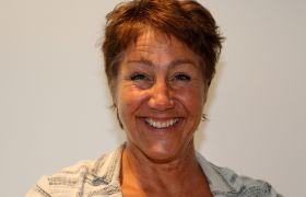 Birgitte Søderstrøm ser i kamera og smiler. Hun har kort brunt hår og en flerfarget jakke på seg.