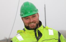 Dan Ragnar Holtan på jobb i steinbruddet med hjelm og oransje vest.