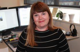 Portrett av Trine Tverbak på kontoret. Hun har langt hår, svart og hvit stripete genser. Sitter foran to dataskjermer.