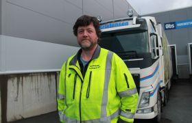 Yrkessjåfør Jan Petter Dalhaug avbildet foran lastebilen sin, iført selvlysende arbeidsklær.