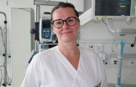 Intensivsykepleier Merethe June Pedersen i hvit arbeidsuniform, med briller, foran monitorer og maskiner på et sykerom.