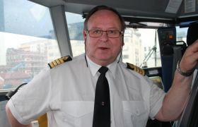 Kaptein Trond Harald Fagermo står på broen ombord i hurtigbåten. Han har på seg kapteinsuniform med hvit skjorte og sort slips.