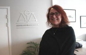 Advokatsekretær Lill Anita Bendiksen foran en grå vegg, hun har på sort genser og briller.