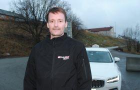 Taxisjåfør Lars Lundquist foran en hvit taxi