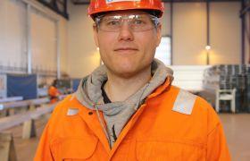Bildet viser aluminiumskonstruktør Eirik Kyvik. Han er avbildet i hallen der han jobber, og er iført hjelm og oransje kjeledress.