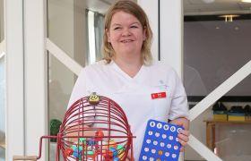 Aktivitør Mari ruller på bingomaskinen på Gjenstad Bo og Aktivitetssenter.