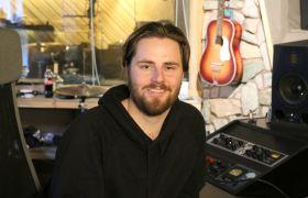 En mann sitter i et musikkstudio med en gitar på veggen.
