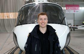 Oskar Emil Olafsen poserer foran et helikopter.