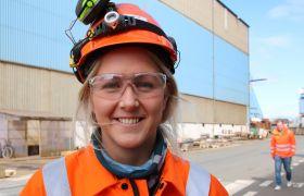 NDT-kontrollør Sara Olsen Tveit er avbildet utenfor en av verkstedshallene der hun jobber. Bildet viser henne fra livet og opp, og hun er iført oransje kjeledress og hjelm med hørselsvern.