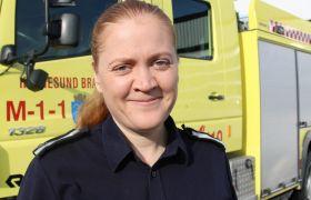 Branningeniør Kathrine Dahle er avbildet foran en brannbil som står utenfor Haugesund Brannstasjon. Hun er iført svart skjorte og er avbildet fra skuldrene og opp.