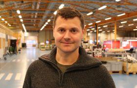 Kenneth Bøhn Müller i en stor hall der han jobber.