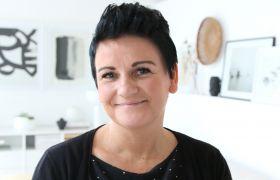 Ann Elin Sørøy i en lys stue med kunst i bakgrunnen.