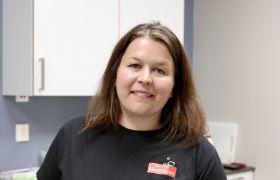 Matteknolog Kari Haugstad er avbildet inne på et av laboratoriene der hun jobber. Hun er iført svart T-skjorte med logo fra Mattilsynet, og er avbildet fra livet og opp. Hun smiler og har mørk, langt hår.
