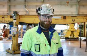 Industrimekaniker Ole Egil Soldal er avbildet inne i en av hallene der han jobber. Han er iført gul og blå kjeledress, hvit hjelm, vernebriller og hansker. Han har mørkt hår og skjegg.
