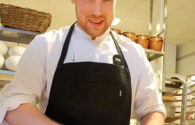Kokk Joakim Ugedal er iført kokkeuniform, han står og jobber ved kjøkkenbenken.