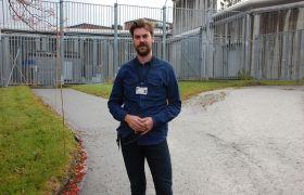 Kriminolog Mats Ravik Jupskås står inne på fengselsområdet med gittergjerde og fengselsmur i bakgrunnen.