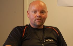 Lufthavnbetjent Jan Ove Fuglem i svart skjorte ser mot kamera.