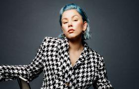 Portrett av sanger Natalie Sandtorv ikledd en rutete dress mens hun sitter på en stol.
