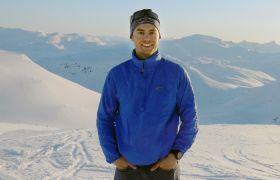 Ørjan på toppen av et fjell med et mange snødekte fjell i bakgrunnen