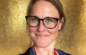Portrett av forgyller Sarah B. Eggen foran en gullvegg.