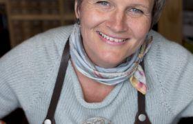 Filigranssølvsmed Gry Marie Grindbakken avbildet ved arbeidsbenken. Hun har på lys grå strikkegenser og sort forkle.