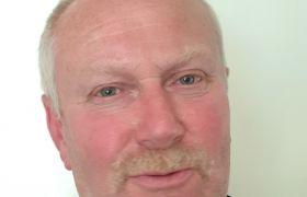 Portrettbilde av bøkker Tor Fjærli, hvit bakgrunn. Han ser inn i kamera.
