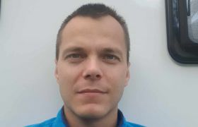 Portrettbilde av CNC-operatør Aleksander Sandhåland i blå overdel hvor han ser rett i kamera, med hvit bakgrunn.