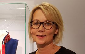 Portrettbilde av duojár Jorunn Løkvold. Hun har på seg briller, en svart overdel og en brosje midt på brystet. Halvveis i bakgrunnen ser vi litt av en blå og rød kofte.