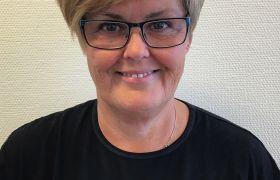 """Portrettfoto av frisør Kristi Helen Furset, iført svart overdel med logoen """"Pitings"""" på i gull skrift. Hun har kort, blondt hår og briller. Ser rett inn i kamera."""
