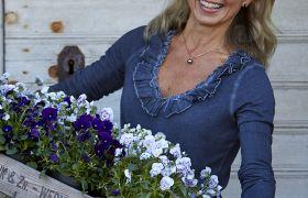 Planteviter Tonje Bergh, i ført blå genser, holder opp en trekasse med blomster og smiler mot kamera.