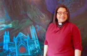 Prest April Maja Almaas står foran et maleri med Nidarosdomen som motiv.