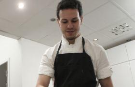 Simon Colombo står bøyd over en benk, han har på hvit skjorte og sort forkle.