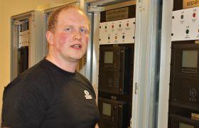 Tavlemontør Kenneth Dalbakk står foran systemskap for brannvarsling som han har bygd.