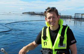 Biolog Torbjørn Gylt i gul redningsvest, med hav og fiskemerder i bakgrunnen. Foto.